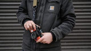 カメラを持つCarharttジャケットを着た男性