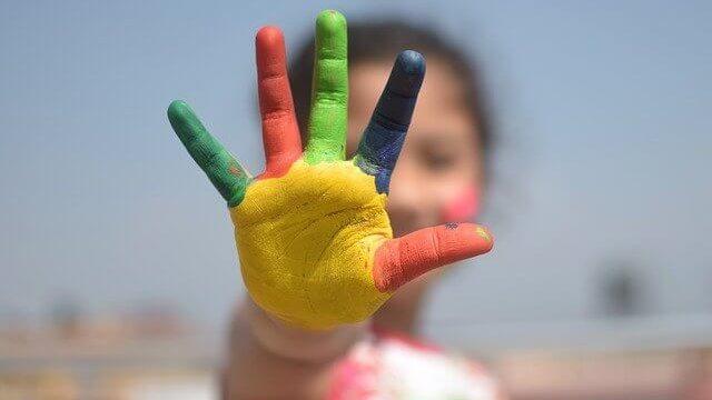 手のひらに黄色赤色緑色紺色の絵具を塗った女性