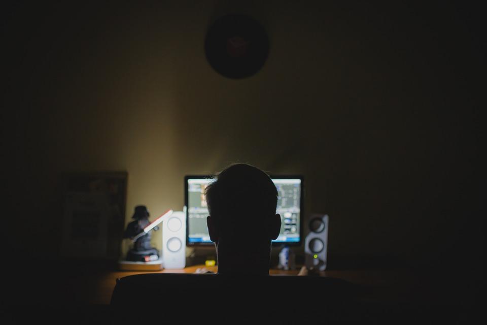 暗い部屋でパソコンを見つめる男性の後頭部